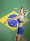 Boczny widok żeńskiej atlety miotania darda przeciw brazylijczyk flaga zdjęcie royalty free