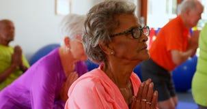 Boczny widok aktywnej rasy starszy ludzie wykonuje joga w sprawności fizycznej studiu 4k zdjęcie wideo