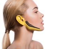 boczny widok atrakcyjna kobieta z kolorem żółtym i czernią maluje na ucho i twarzy obraz royalty free