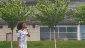 Boczny widok atrakcyjnego młodego uśmiechniętego amerykanina afrykańskiego pochodzenia biznesowa kobieta opowiada na telefonie ko zdjęcie wideo