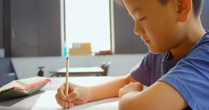 Boczny widok baczny Azjatycki uczniowski studiowanie przy biurkiem w sali lekcyjnej przy szkołą 4k zdjęcie wideo