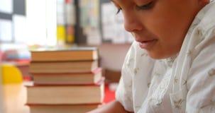 Boczny widok baczny Azjatycki uczniowski studiowanie z laptopem w sali lekcyjnej przy szko?? 4k zdjęcie wideo