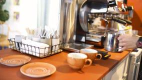 Boczny widok barista w błękitnej szkockiej kraty koszula przygotowywa cappuccino lub latte w jego coffeeshop sztuka Stawiać mleko zbiory