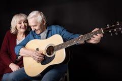 Boczny widok bawić się gitarę z żoną blisko starszy mężczyzna obok Obrazy Stock