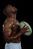 Boczny widok bez koszuli męskiej atlety mienia rugby przyglądająca up piłka Fotografia Royalty Free