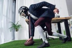 boczny widok biznesmen w rugby hełmie bawić się futbol amerykańskiego zdjęcie stock