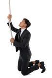 Boczny widok biznesmena ciągnięcia arkana podczas gdy klęczący Zdjęcia Stock