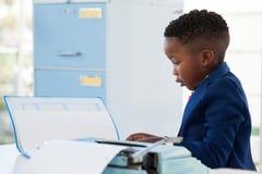 Boczny widok biznesmena czytania dokument podczas gdy pracujący Zdjęcia Royalty Free