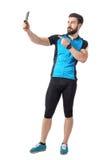 Boczny widok cyklista w błękitnej dżersejowej koszulce bierze selfie i wskazuje palec przy telefon kamerą Fotografia Stock