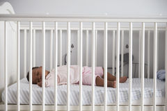 Boczny widok dziewczynki dosypianie W pepiniery łóżku polowym Obraz Stock