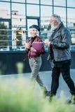 boczny widok elegancka starsza para z kawą iść chodzić Obrazy Stock