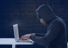 Boczny widok hacker używa laptop przed błękitnym tłem Obraz Stock
