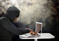 Boczny widok hacker używa laptop przed czarnym tłem Zdjęcia Stock