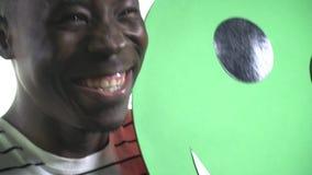 Boczny widok jako rozochocony murzyn podnosi zielonego smiley, gryźć zwolnione tempo zdjęcie wideo