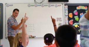 Boczny widok Kaukascy m?skiego nauczyciela nauczania schoolkids na whiteboard w sali lekcyjnej 4k zbiory