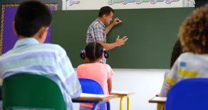 Boczny widok Kaukascy m?skiego nauczyciela nauczania schoolkids na whiteboard w sali lekcyjnej 4k zbiory wideo