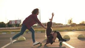 Boczny widok kobieta z ona ręki podnosił up siedzieć na longboard podczas gdy jej przyjaciel pcha ona i biegać behind zdjęcie wideo