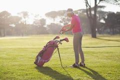 Boczny widok kobiety kładzenia kij golfowy w torbie Obraz Stock
