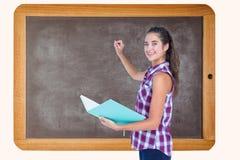 Boczny widok kobiety mienia książka podczas gdy pisać na blackboard Fotografia Royalty Free