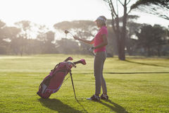 Boczny widok kobiety przewożenia kij golfowy Fotografia Stock