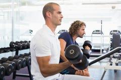 Boczny widok mężczyzna ćwiczy z dumbbells w gym Fotografia Royalty Free
