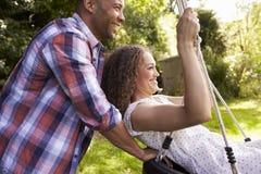 Boczny widok mężczyzna dosunięcia kobieta Na opony huśtawce W ogródzie Obraz Royalty Free