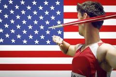 Boczny widok męska atlety miotania darda przeciw flaga amerykańskiej obraz stock