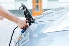 Boczny widok męska ręka ładuje elektrycznego pojazd Obrazy Royalty Free