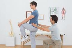 Boczny widok męski physiotherapist egzamininować obsługuje z powrotem Fotografia Royalty Free