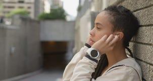 Boczny widok młoda amerykanin afrykańskiego pochodzenia kobieta jest ubranym słuchawki w mieście 4k zbiory wideo
