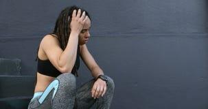 Boczny widok młoda amerykanin afrykańskiego pochodzenia kobieta relaksuje na krokach w mieście 4k zbiory wideo