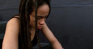 Boczny widok młoda amerykanin afrykańskiego pochodzenia kobieta relaksuje na krokach w mieście 4k zbiory
