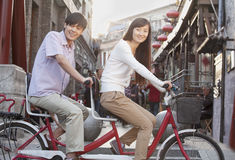 Boczny widok Młoda Heteroseksualna para Patrzeje kamerę na Tandemowym bicyklu w Pekin Obraz Stock