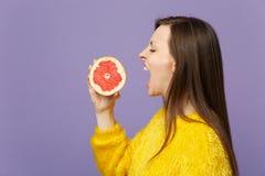 Boczny widok młoda kobieta w futerkowym puloweru mieniu w ręce, zjadliwa połówka świeży dojrzały grapefruitowy odosobniony na fio obrazy royalty free