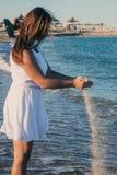 Boczny widok młoda piękna nikła dziewczyna podziwia błękitną ocean pozycję na z płaskim brzuchem i round łupem zdjęcie royalty free