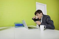 Boczny widok młody biznesmena łasowanie podczas gdy używać laptop przy stołem Obraz Royalty Free