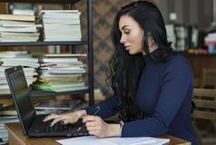 Boczny widok Młody biznesowej kobiety obsiadanie przy stołowymi i biorą notatkami w notatniku Na stole jest laptop Studencki ucze Obrazy Royalty Free