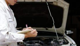 Boczny widok młody fachowy mechanik w jednolitym writing na schowku przeciw samochodowi w otwartym kapiszonie przy remontowym gar obrazy royalty free