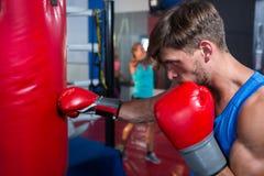 Boczny widok młody męski bokser uderza pięścią czerwoną torbę obraz stock