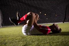 Boczny widok młody męski gracza piłki nożnej cierpienie od kolano bólu Obraz Stock