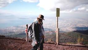 Boczny widok młody piękny żeński turysta wycieczkuje w dół od Vesuvius wulkanu cieszy się widok Naples z plecakiem zbiory wideo