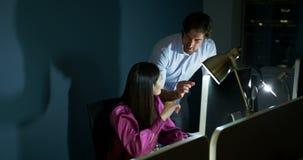 Boczny widok młodzi Kaukascy biurowi kierownictwa pracuje na komputerze przy biurkiem w nowożytnym biurze 4k zdjęcie wideo