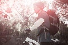 Boczny widok męski halny rowerzysta z bicyklem w lesie Obraz Stock