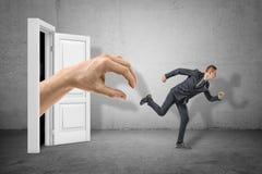 Boczny widok malutki biznesmena bieg od ogromnej ręki wyłania się od drzwi za obraz stock