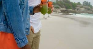 Boczny widok Mieszany biegowy pary mienia koktajlu napój na plaży 4k zdjęcie wideo