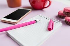 Boczny widok na żeńskim biurku Telefonu i francuza macarons na modnym różowym biurku Fotografia Royalty Free