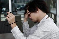 Boczny widok niespokojny sfrustowany młody Azjatycki biznesowego mężczyzna obsiadanie i wzruszający czoło z rękami obraz stock