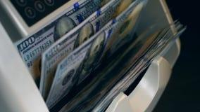 Boczny widok odliczająca maszyna z dolarami w nim zbiory