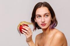 Boczny widok odosobnienie Atrakcyjny dziewczyny mienie wewnątrz wręcza czerwonego jabłka na którym siedzi iguana gekonu Fotografia Stock