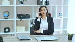 Boczny widok opowiada przy telefonem i obsiadaniem stołem z laptopem w biurze Biznesowa kobieta zdjęcie wideo